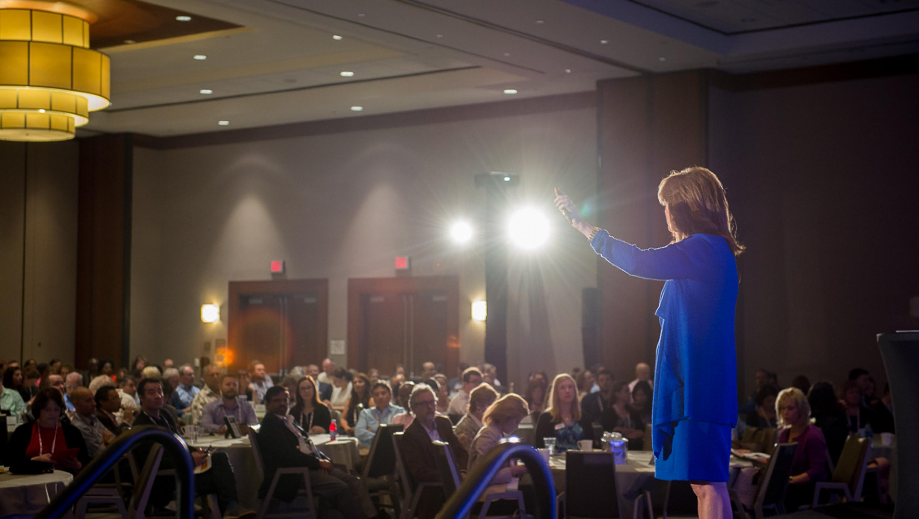 A picture of APQC staff member Cindy Hubert keynoting at APQC's Annual KM Conference